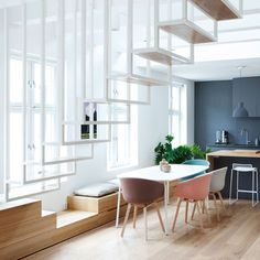 The white steel staircase suspended in the centre of this renovated Oslo loft is completed by a piece of wooden furniture that also functions as a chest of drawers and a window seat.