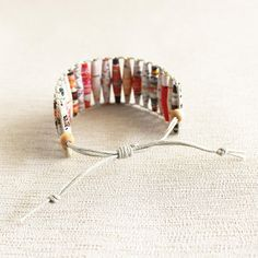 This eco friendly bracelet is made of paper beads handcrafted from an art magazine. The beads have been aesthetically put together in delightful shades of pink and peach. The paper beads are given a coat of eco friendly sealant to make it sweat and splash proof. The beads are strung