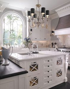 "love this - are my ceilings not tall enough? Love the heather gray stove hood. Not crazy about the ""x"" drawers in the island but I like the idea of using that space for food bins"