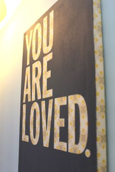 You are Loved. Nursery art. DIY painting. Just wrap fabric over a canvas. Put letter stickers on it. Paint over the whole thing. Peel off stickers