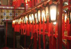 Red lanterns hanging in a row cast a golden glow inside Mo Man Temple in Hong Kong on November (Tahiat Mahboob) Red Lantern, Surface Design, Light Up, Hong Kong, Lanterns, Temple, November, Glow, It Cast