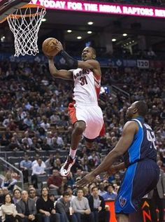 Toronto Raptors forward Terrence Ross, left, slam dunks the ball past Dallas Mavericks Elton Brand, right, during first half NBA basketball action in Toronto on Friday, Dec. 14, 2012. (AP Photo/The Canadian Press, Nathan Denette)