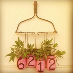 DIY house number fashioned from an old rake head, plantings in mason jars marked with chalk paint. Via @alleinenadalkhalifa on Instagram