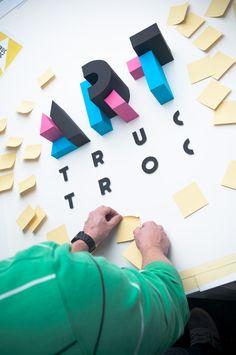 """Trabalho muito bacana feito pelo pessoal da INK studio, com uma característica que acho bem interessante, e sempre tento incentivar no blog, que é o retorno de se fazer as coisas a mão e depois fotografar. Neste caso eles fizeram várias figuras geométricas de papel, que formam a palavra """"ART"""", para ilustrar a identidade do evento."""