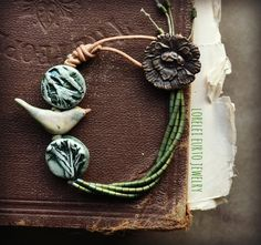 The amazing Lorelei Eurto : Ceramic bird- Kylie Parry Ceramic coins- Mary Harding Grass green coated hematite tube beads Brass Peony button Linen cording Round leather cording meausres 7-1/4 inches Bird Jewelry, Ceramic Jewelry, Clay Jewelry, Jewelry Crafts, Jewelry Art, Beaded Jewelry, Jewelry Design, Jewellery, Artisan Jewelry
