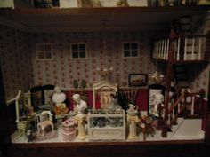 This is a series of photos showing the progress of a very talented miniaturist turning a bookshelf into a three story urban shop.