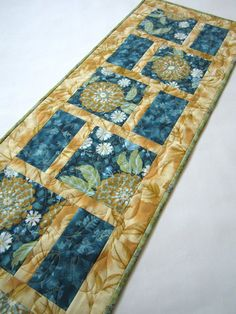 This table runner is stunning with the teal main color fabrics outlined by a gold leaf fabric. I beautiful runner that will look great in your room. Give this as a gift to someone. This table runner i
