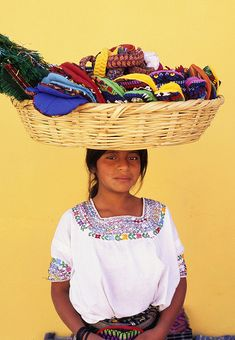 A young Maya woman sells textiles in the town of Antigua, Guatemala