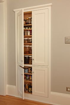"Tap into stud space for more wall storage - ""If you've got an unused wall in your kitchen, consider using it to store canned goods and jars, as seen here, or stemware, vases and serving pieces. Notice the trim and the door design, which not only conceal the storage but add interest to an otherwise blank wall. Though cost will vary, Deidra Anderson, marketing administrator at David Heide Design Studio, says this project cost $1,300 to $1,900."""