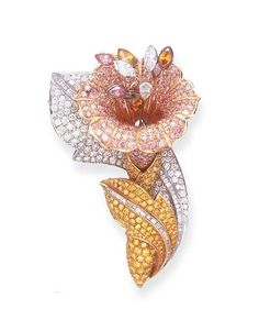 A COLORED DIAMOND FLOWER BROOCH