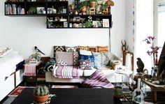 Pokój z sofą pełną poduszek i tekstyliów. Półki z eklektyczną mieszanką książek i pamiątek