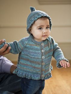 Adorable and elfin, this cardigan and bonnet set has bell shaped motifs at all its edges. The hat comes to a point and ties under baby's chin.