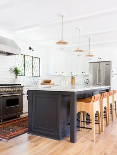 Stunning modern bohemian open plan kitchen with tuxedo cabinets (white cabinets on top, and a black kitchen island in the middle) with modern wood bar stools, brass pendant lights and a vintage kilim rug runner. Gorgeous classic California style. See more of this California Eclectic Home by Amber Interiors on My Domaine!