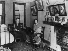 November 1923: A family in their room in a Lisburn Street tenement house in the Bethnal Green slum area. (Photo by Topical Press Agency/Getty Images)