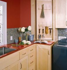 This laundry room/potting room has red walls and mosaic tiles.