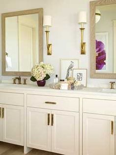 Classic white bathroom with gold accents [ sconces, mirror, faucet and hardware ] Love the furniture style base on the vanity cabinets.