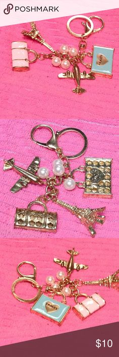 Handbag & Keychain Decor We are off to Paris with this beautiful Charm keychain & handbag decor. Charms feature a pink enamel handbag. Turquoise enamel suitcase with gold heart with the words travel, a jet plain & a Bling, Bling, crystal Eiffel Tower with additional pearl charms decorating this statement piece.  Gold hardware. BNWOT Accessories