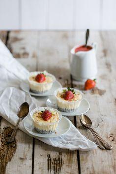 Mini New York Cheesecakes mit Erdbeeren und Müsliboden wunderschön auf einem Holztisch angerichtet. Ausgewählte Zutaten für Deine Backwaren findest Du online in unserem Shop: https://gegessenwirdimmer.de/produkt-kategorie/kochen-backen-und-feinkost/#backen