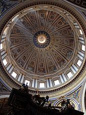 St. Peter's Basilica - Photo looking up at the dome's interior from below. The dome is decorated at the top with a band of script. Around its base are windows through which the light streams. The decoration is divided by many vertical ribs which are ornamented with golden stars.