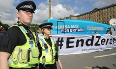 Police stand by as protesters unfurl a large banner against zero hours contracts in front of the Conservative Party 'battle bus' in Halifax in northern England