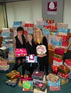 Acorn Stairlifts staff surrounded by the gifts they have collected for Childrens home