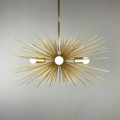 This gold urchin chandelier is a mixture of matte gold steel spines and plated brass finishes and is a warm statement piece well suited to spaces traditional, midcentury, and more. Note: Fixture newly upgraded starting 2017 to include all larger medium base (E27) sockets (total 4) to provide more light than previous designs which used candelabra (E12) sockets. Lead time: 2-3 weeks  Measurements: - Diameter: 27 in (or 31 in) - Height: 12 in (Height remains 12 in for 31 in version) - Weight: 8…