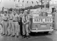 """George Lincoln Rockwell, center, self-styled leader of the American Nazi Party, and his """"hate bus"""" with several young men wearing swastika arm bands, stops for gas in Montgomery, Alabama, on May 23, 1961, en route to Mobile, Alabama."""