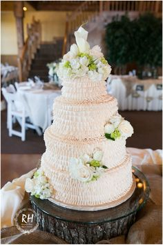 White ruffled 4-tier wedding cake trimmed with fresh florals. Grande Hall at Hofmann Ranch, Castroville TX