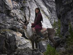 A deermaid poses for a photo on rocky cliffs in Mongolia