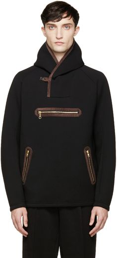 Long-sleeve hooded neoprene jacket in black. Brown suede trims throughout. Single-button closure at collar. Raglan sleeves. Three welt pockets at front with gold-tone zippers. Hood lined in contrasting heather grey. Tonal stitching.