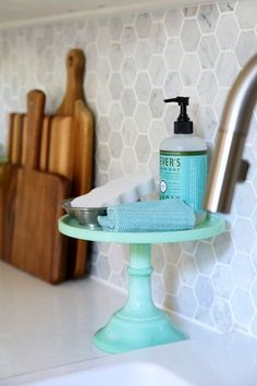 Use a cake stand to organize kitchen cleaning supplies, Carra marble backsplash. Beautiful white IKEA SEKTION GRIMSLOV kitchen with aqua and green accents, a gorgeous marble hexagon backsplash, and quartz countertops