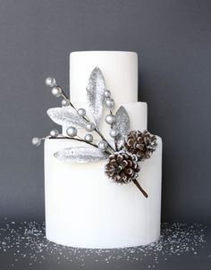 Simple yet stunning white cake with silver leaves, balls and dusted pinecone accent