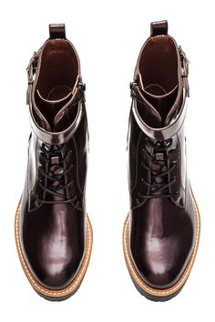Vysoké boty: Koženkové kotníkové boty s předním šněrováním. Mají ozdobný horní pásek s kovovou přezkou a boční zip. Saténová podšívka a koženková stélka. Masivní gumová podrážka. Výška podpatku 4 cm.