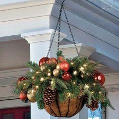 a hanging arrangement wwith ornaments, lights and evergreens