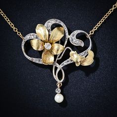 Art Nouveau Brooch - This lovely necklace harkens from the very early 20th century and consists of a subtly enameled diamond set flower and bud with classic whiplash curves sparkling with tiny rose cut diamonds like the dew on a branch. A small natural fresh water pearl gracefully dangles completing the necklace.