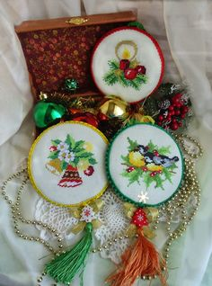 cross stitched Christmas ornaments with bells, candles and birds