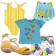 Outfit per una bimba al mare! Costume intero in giallo. Short super colorato, T-shirt azzurra con applicazioni, sandali in pelle con zeppa in sughero. Simpatico cappellino!