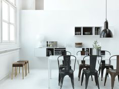 Black Tolix chairs around white dinning table
