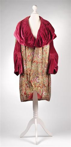 1920s coat, gold silk brocade with floral decoration, burgundy silk velvet, salmon silk lining, sleeves and shawl collar with elaborately smocked parts. (hva)