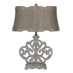 """Illuminate your bedside or living room decor with this elegant table lamp, showcasing an openwork base and linen drum shade with scalloped details and scrolling embroidery.   Product: Table lampConstruction Material: Linen, wood and metalColor: Aged white over silver and naturalFeatures:  Openwork baseDrum shadeScalloped details Scrolling embroidery 3-Way switch  Accommodates: (1) 100 Watt bulb - not includedDimensions: 25.25"""" H x 18"""" W x 10"""" D"""