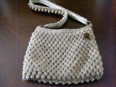 Crocheted purse.  Off-white crocheted bag done all over with bobbles, fully lined, zipper closure featuring a wooden beaded bead for a pull.  Bobble strap lined with the same fabric as the purse lining.