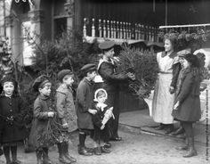 1918: A young sailor buys a Christmas tree at a greengrocers and a young boy waits in a queue of children to buy some mistletoe