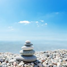 Stack of zen stones over sea and clouds background - By Inari Griffin