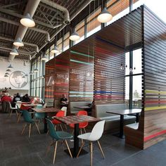 Nike Office (Netherlands) Design Studio: UXUS Dining area with slatted booths adorned with painted logos