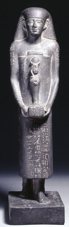 Grey basalt theophorous statue of Wennefer carrying a small figure of Khonspakhered. 26th dynasty. (Incised hieroglyphic text on the back-pillar [two columns]; upper arms, skirt and plinth.)