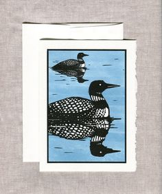 """Blank greeting card of two loons on a still lake. Designed by New Hampshire artist Katharine Woodman-Maynard in her distinctive wood-cut style.  FREE SHIPPING on orders in the USA.  DETAILS * The card is printed on heavy, lovely, Strathmore white card stock, which is lightly textured with a deckled edge * Boxes of Cards are packaged in a kraft box with a clear plastic lid and tied with bakers twine * Folded card, blank on the inside. Matching envelope with square flap * Card measures: 5"""" x…"""