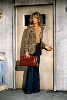 Farrah Fawcet wears a sport jacket with her feathered hair and leather bag - all very 70s styles, yet women wearing suits was still slightly unpopular with the masses until the 80s.