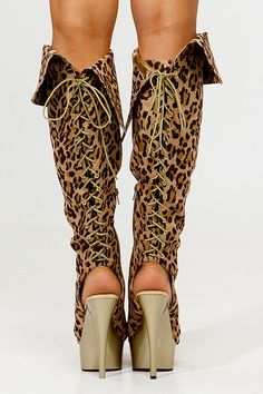 Knee high lace up back leopard print heeled boots.