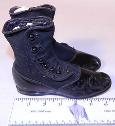 """High button child's shoes, 1890. They are made of a two tone black wool fabric top and black patent leather bottom shoe, with 7 black buttons down the side for closure. There are rounded toes, a low heel and hard leather black soles stamped on the bottoms size 7.5. The boots measure 5"""" tall, 7"""" long and are 2"""" wide."""