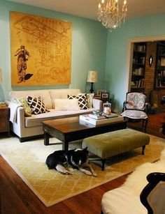 Love the light blue wall and goldenrod accent, the wood floors, and the mostly neutral furniture.  Not sure how I feel about the random chandelier.
